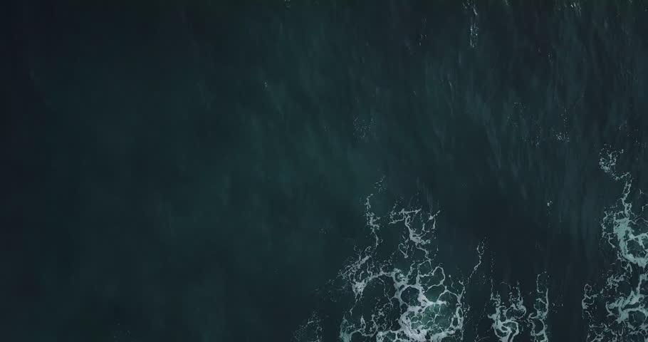 Aerial top view waves break on dark rocks near beach. Sea waves on the dangerous stones aerial view drone 4k shot. Bird's eye view of ocean waves crashing against an empty beach from above. | Shutterstock HD Video #1013835875