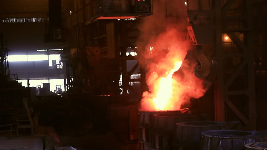 Molten pour of hot metal in a Steel Mill Factory from a Crucible into a Mold