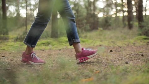 Teenager walks in pine trees forest wearing pink sneakers shoes slow motion closeup side ground view. Girl in jeans and cute trainers step on park path spring evening or early morning sun shine nature