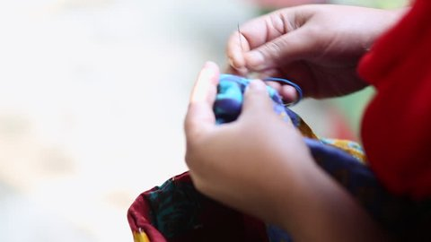 Bangladesh woman sewing a handle together for a traditional bag