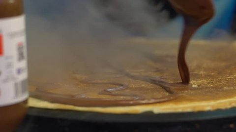 Slow motion vendor man cooking crepes on a metal griddle in Paris street. Close-up of pancake with chocolate dessert. Delicious fast food. A hand is making crepe outdoors. Cheff cook a tasty crepe-Dan