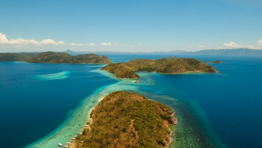 Aerial view: Lagoon with blue, azure water in the middle of small islands and rocks, Palawan. Beach, tropical island, sea bay and lagoon, mountains with forest, Coron. Busuanga. Seascape, tropical