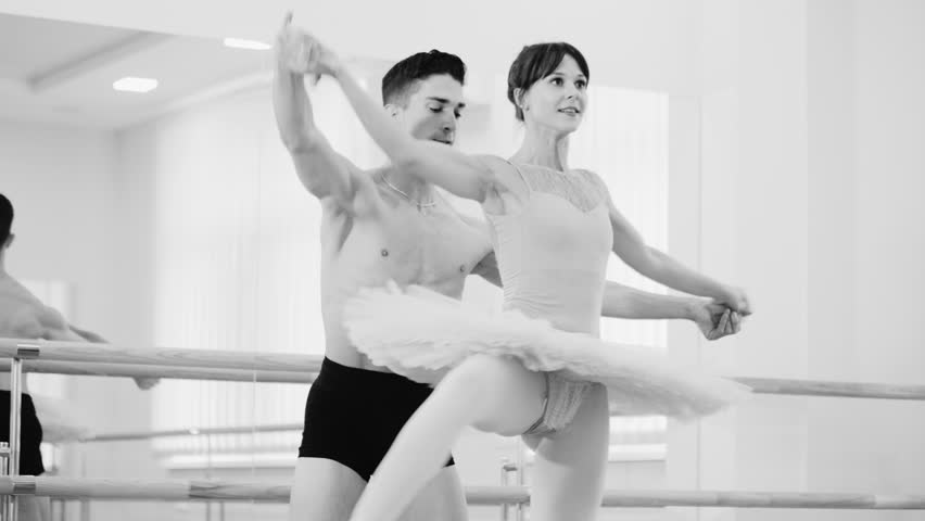 Repetition in ballethall. Young sensual couple in costumes dancing together. Man rotates ballerina around axis, supporting her around waist. Slow motion. Black and white | Shutterstock HD Video #1013858495