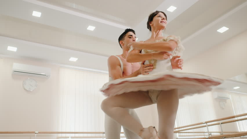 Repetition in ballethall. Young sensual couple in costumes dancing together. Man rotates ballerina around axis, supporting her around waist. Slow motion. 4k | Shutterstock HD Video #1013858525