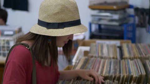 Young woman in hat looking through vinyl records