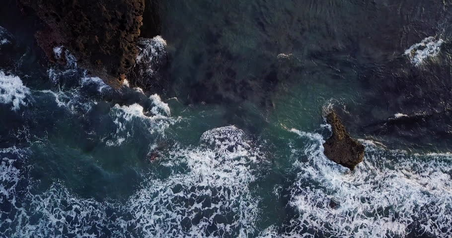 Aerial top view waves break on dark rocks near beach. Sea waves on the dangerous stones aerial view drone 4k shot. Bird's eye view of ocean waves crashing against an empty beach from above.