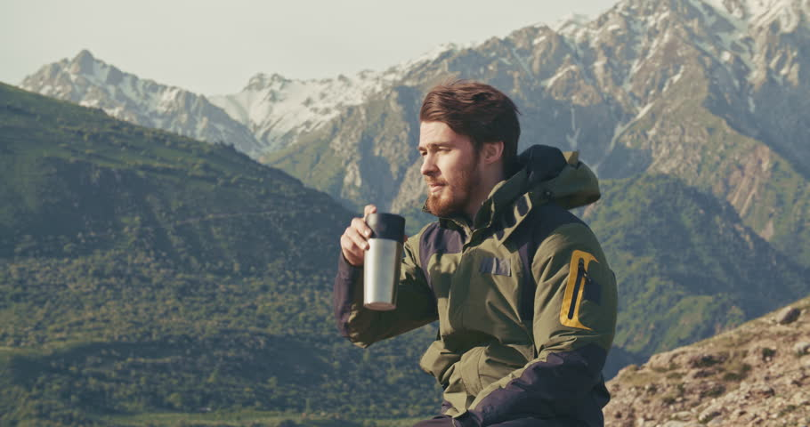 lonesome climber sitting on top of mountain, drinking coffee in thermos. adventurer relaxing after achieving a goal. zen, freedom concept 4k