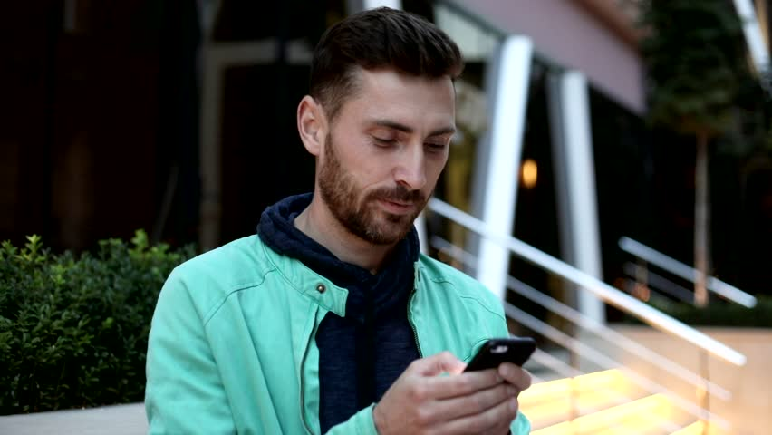 Happy and Satisfied Man Standing in the Street. Holding a Modern Mobile Phone.Chatting on it. Standing near the Glass Building's Entrance. Casual Outfit. Evening Walk. Pleasant Mood. | Shutterstock HD Video #1013880365