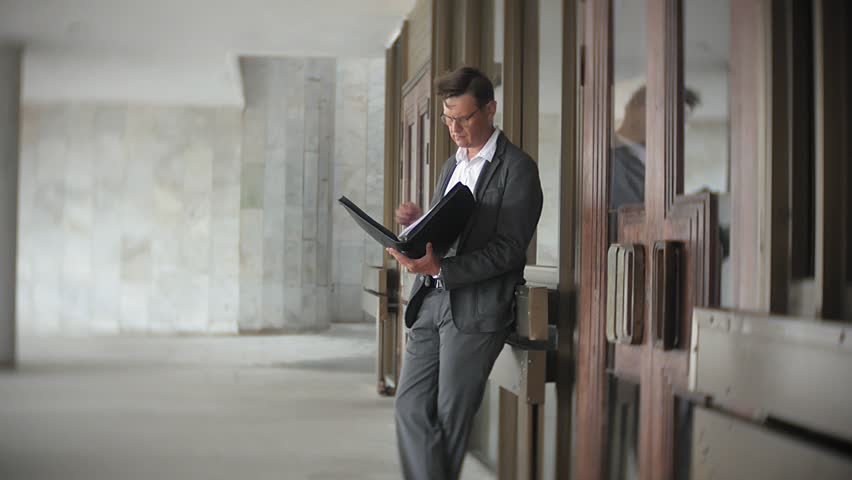 A young, respectable businessman sent to an office building. In his hands he holds a briefcase, looks through documents. 4k | Shutterstock HD Video #1013883905