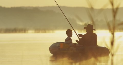 Old angler in a hat with a grandson sitting in the boat in the cane on the lake at the dawn with a rod while fishing. Outside.