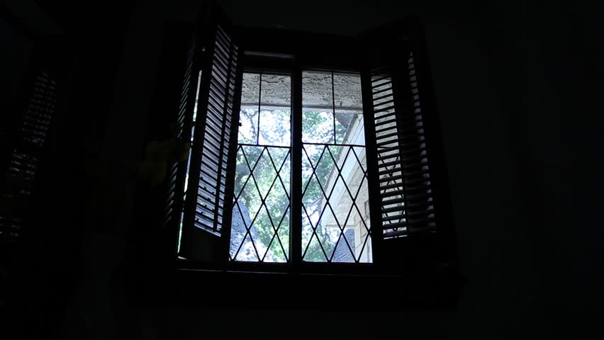 Wide shot of a silhouetted, masked intruder in black as he peers ominously through the window of a house from the outside.