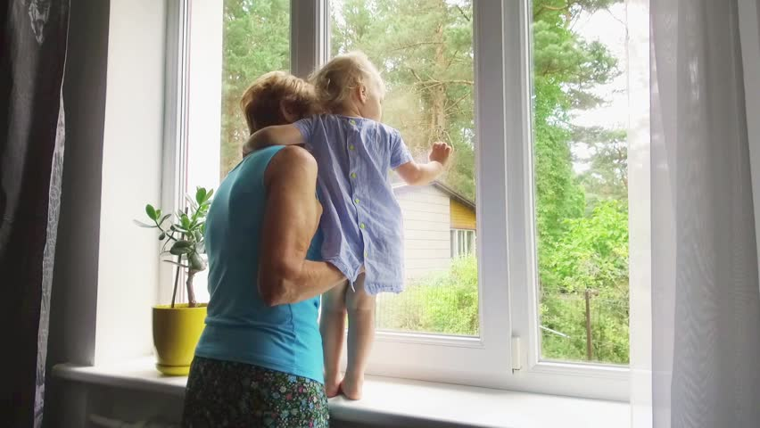 grandmother playing and taking care of child at home. looking through the window #1013899175