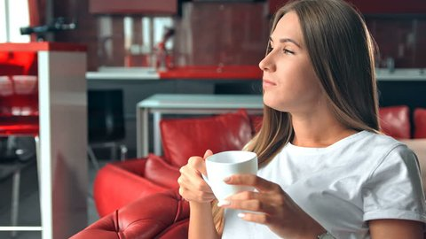 Young woman sitting on a chair and drinking coffee in red stylish appartment