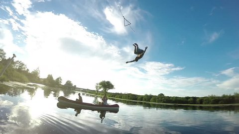 SLOW MOTION: Friends film playful man doing a backflip off rope swing into the calm river flowing through the picturesque countryside. Awesome shot of tourist jumping into cold stream in the summer.
