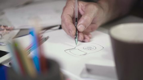 Hands of the famous artist draw a weight for sixteen kilograms. Men's hands draw a sketch of a sixteen-kilogram weight