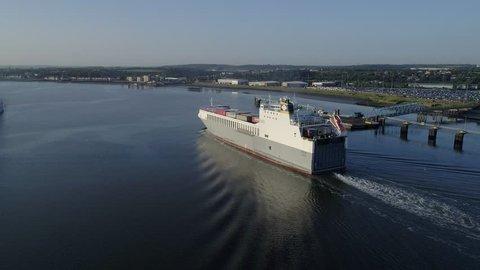 Aerial camera follows ro-ro cargo ship Adeline along Thames near Dartford England