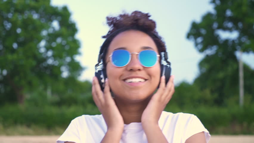 HD follow shot video of beautiful mixed race African American girl teenager young woman in white T-shirt and blue sunglasses walking listening to music on wireless headphones