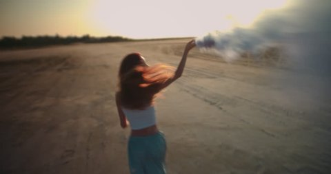 Young woman running with smoke bomb and celebrating at music festival in desert