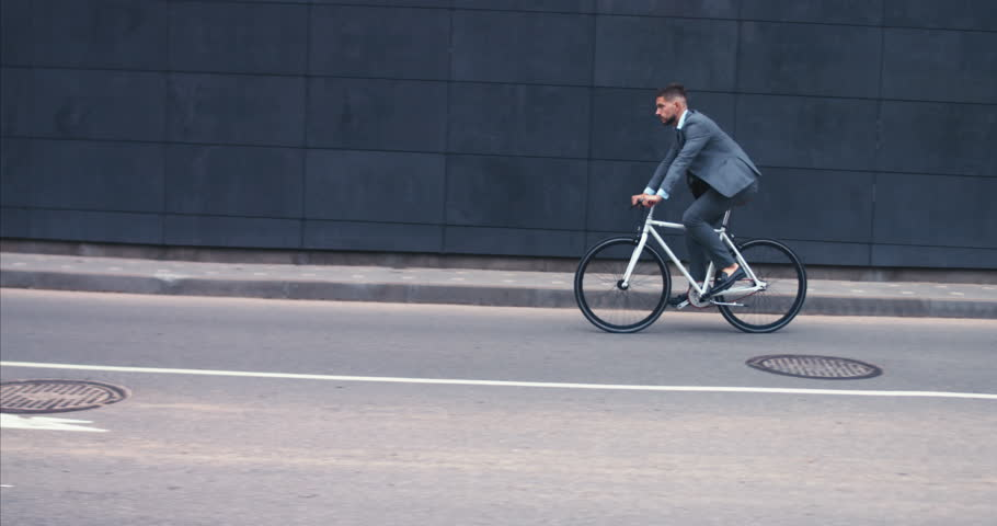 TRACKING Handsome young adult man wearing suit riding his classic bicycle to work in the morning. 4K UHD 60 FPS SLOW MOTION | Shutterstock HD Video #1013989835