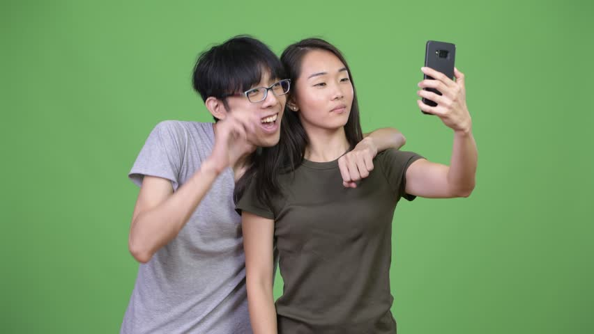 Young Asian couple using phone together   Shutterstock HD Video #1013990855