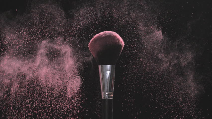 Two Make-up brushes with pink powder on a black background
