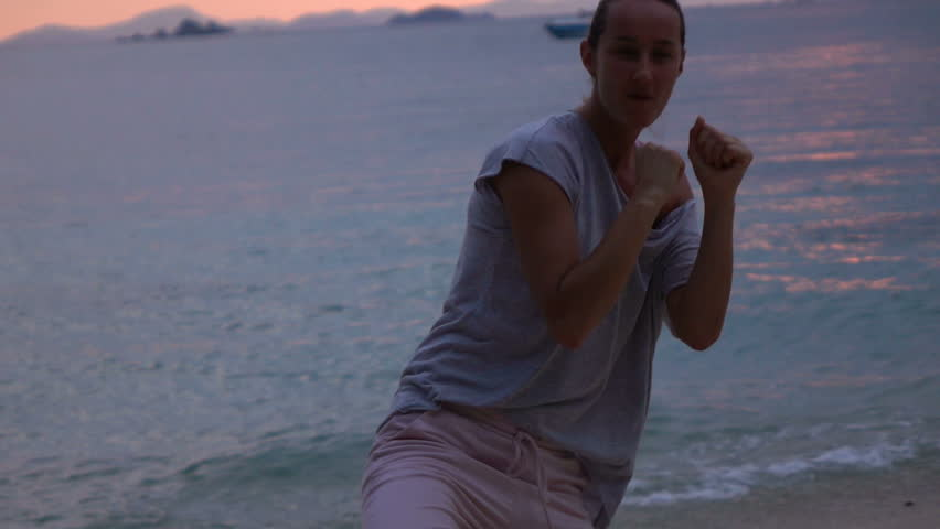 Woman exercising, kicking leg on the beach in the evening, super slow motion 240fps  #1013993285