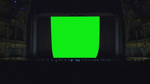 On the stage of the theater, the light goes out, the curtain opens against a green background, green screen, chroma key