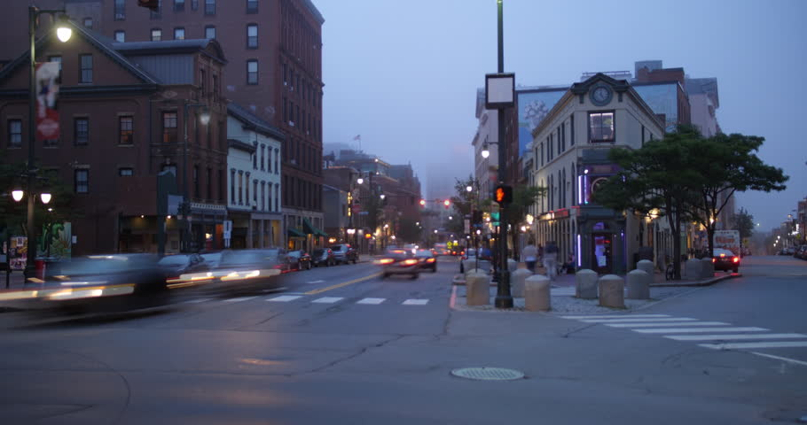 A night time lapse view of downtown traffic and businesses along Congress Street in Portland, Maine on a foggy evening.