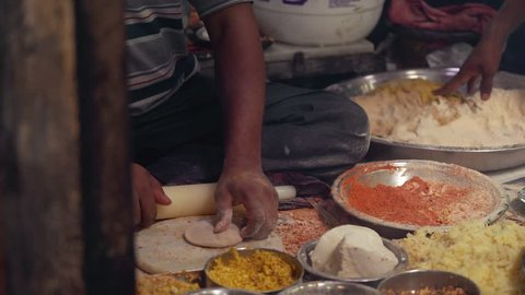 street food market in india - hands preparing spicy dough with rolling pin