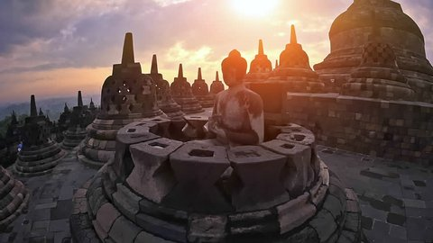 Exploring beautiful Borobudur temple in Java Indonesia at sunset. Buddha statue in traditional buddhist stupa peaceful meditating background
