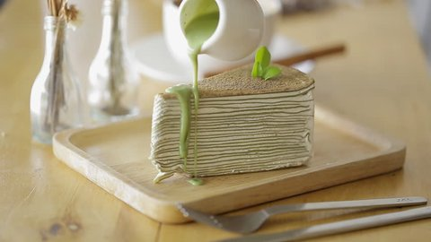 Cutting Green tea crepe cake with knife on wooden plate.