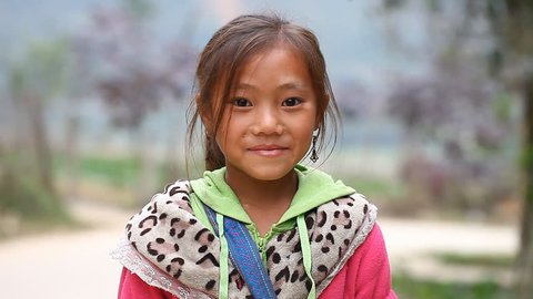 Sapa, Vietnam - November 30, 2016 : A little girl from the ethnic group of Hmong poses the foreigner for the camera. Children often pose for this purpose to earn reward or to sell the souvenirs.