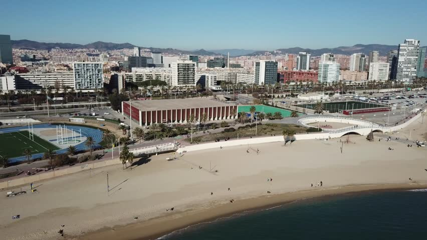 Aerial view of the beautifull beaches of Barcelona, Spain, in winter. Drone flies over the beaches Llevant and Mar Bella facing the modern district Diagonal Mar with its skyscrapers