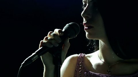 Silhouette of a beautiful girl singer with microphone in the dark.
