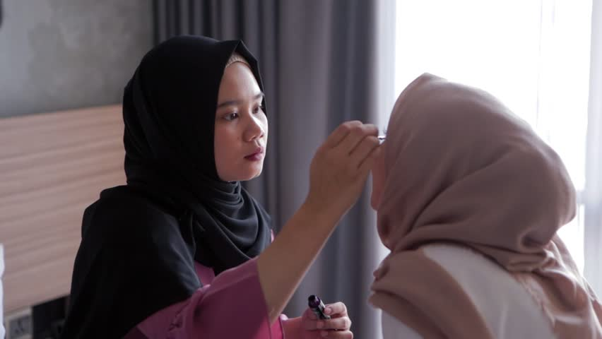 Makeup artist applying mascara on eye lashes of model. Modern life of muslim people. Edited and raw.