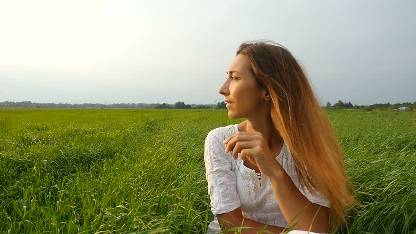 Portrait happy young woman on a summer walk in field. Cute girl sitting on the green grass and dreaming. Beautiful young woman enjoying nature in summer evening. Grassy summerfield   | Shutterstock HD Video #1014099785