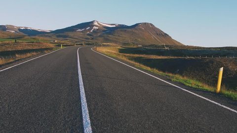Drivers perspective of mountain road in Iceland, POV, view from car window, moving backwards