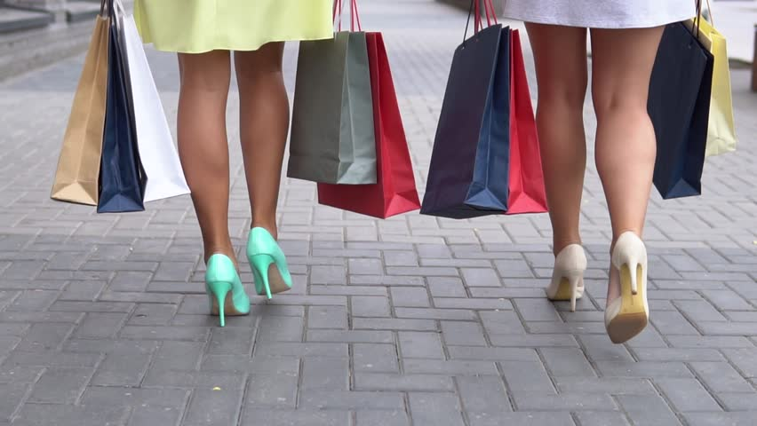 Two girlfriends carry packages of different colors with shopping after shopping walking down the street. slow motion. HD | Shutterstock HD Video #1014126125