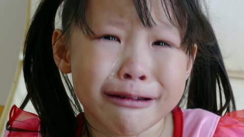 Little Asian girl crying at home