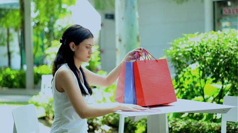 Young sick woman having a heart attack, she try to call with smartphone before senseless in the garden of shopping mall