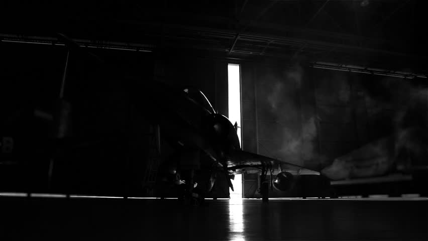 Fighter Aircraft in a Hangar. The Door Opens. Black and White Tone.