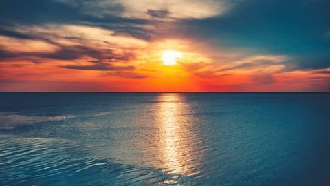 Beautiful sunset over ocean with sun reflection. Bright color toning. Nature landscape. Holidays, travel, vacation. Water waves movement and clouds in sky float. 4K Slow Motion Time Lapse Parallax