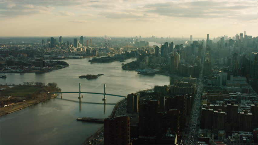 Aerial view of New York City. Flying over river and buildings at sunset. Shot with a RED camera.
