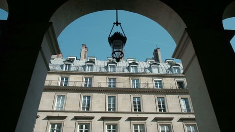 Tracking right view between colonnade arches of typical Parisian style building near Place Vendome in Paris, France
