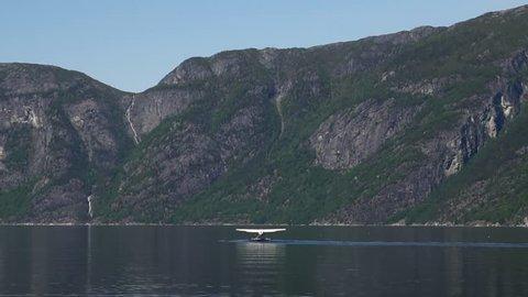 Small white floatplane taking off towards the mountains in Eidfjord, Norway.