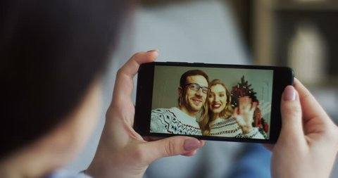 Web cam chatting of the brunette woman with her Caucasian cheerful couple of friends near Christmas tree on the black smartphone. Close up.