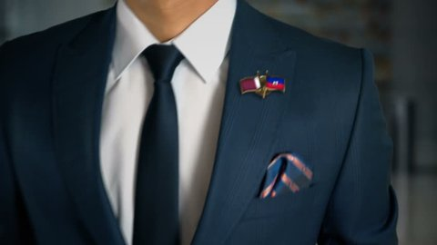 Businessman Walking Towards Camera With Friend Country Flags Pin Qatar - Haiti
