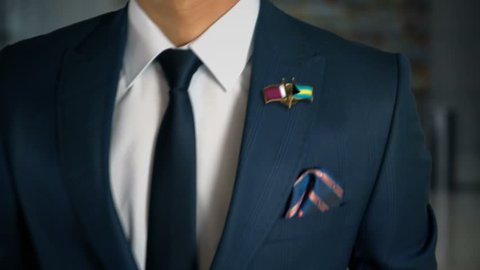 Businessman Walking Towards Camera With Friend Country Flags Pin Qatar - Bahamas