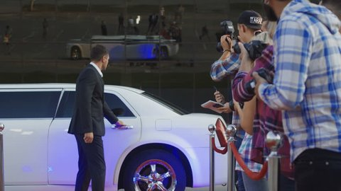 Celebrity woman in red dress walking out of limo, giving autograph, and taking shot with fan on red carpet