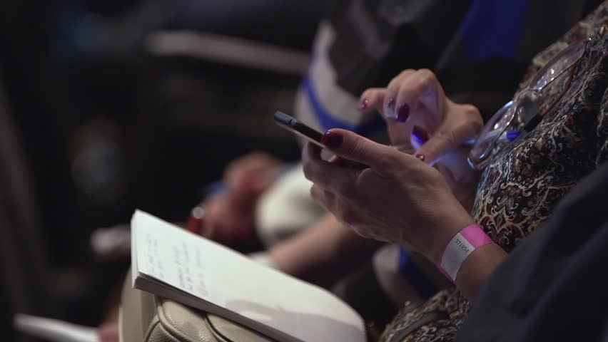 Girl with notepad sits in conference room and scrolls the screen. Stock. Closeup of female hands are typing sms on smartphone. Closeup of female hands scrolling something in the smart phone